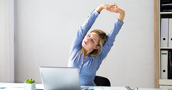 Frau streckt Arme während der Arbeit am Laptop